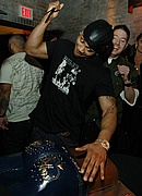Nelly cutting the cake at the Apple Bottoms 5th anniversary party